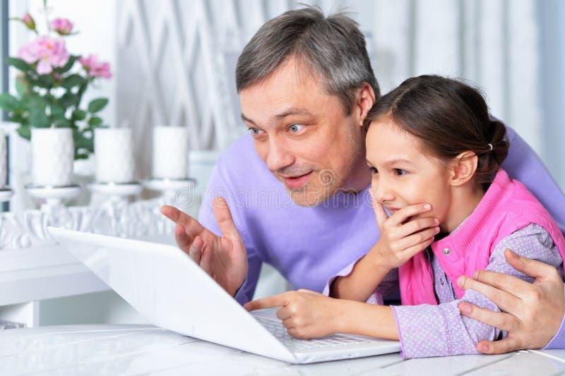 Retrato del padre con poca hija que usa el ordenador portátil fotografía de archivo