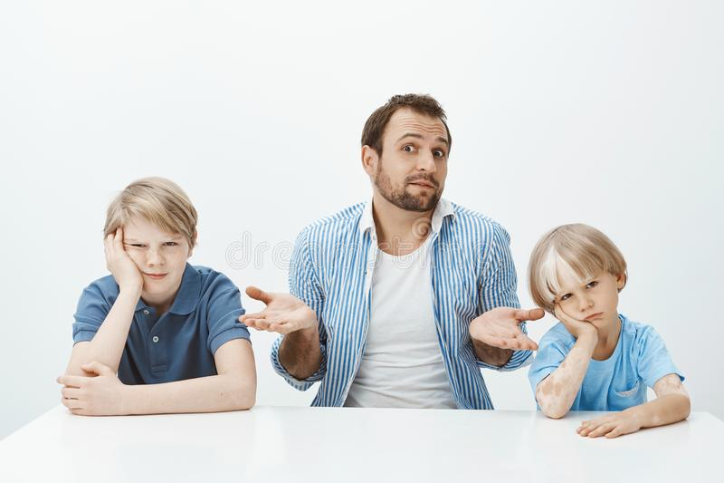 Retrato del padre europeo inconsciente confuso que se sienta con los hijos en la tabla, encogiendo con las palmas separadas y pre fotos de archivo libres de regalías