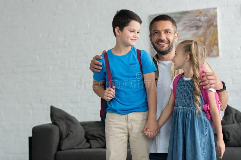 retrato del padre sonriente que abraza a niños con las mochilas en casa de nuevo a imagenes de archivo
