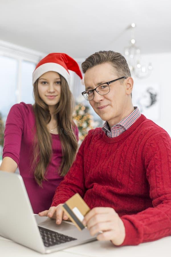 Retrato del padre y de la hija que hacen compras en línea durante la Navidad fotografía de archivo libre de regalías