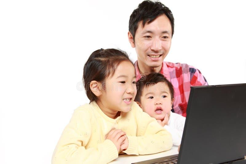 Retrato del padre y de niños japoneses en el ordenador portátil foto de archivo