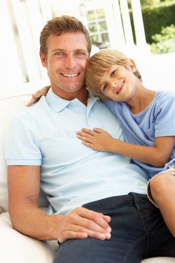 Retrato del padre y del hijo que se relajan en el sofá imagenes de archivo