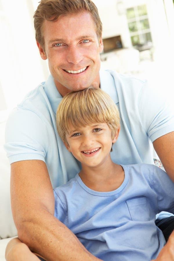 Retrato del padre y del hijo que se relajan en el sofá foto de archivo