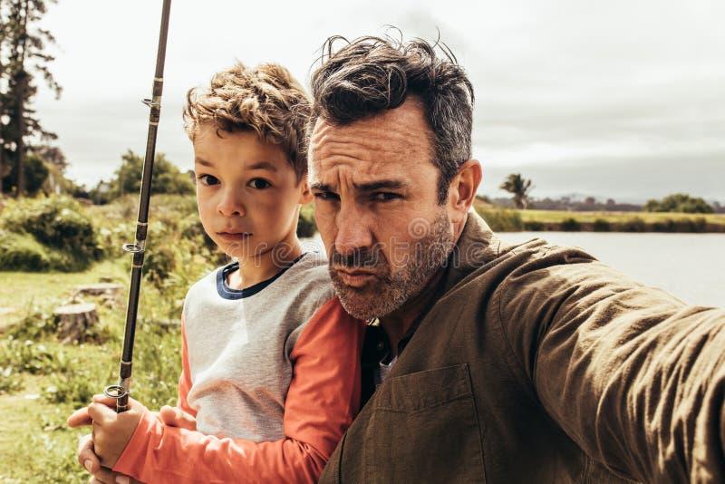 Retrato del padre y del hijo hacia fuera para pescar foto de archivo