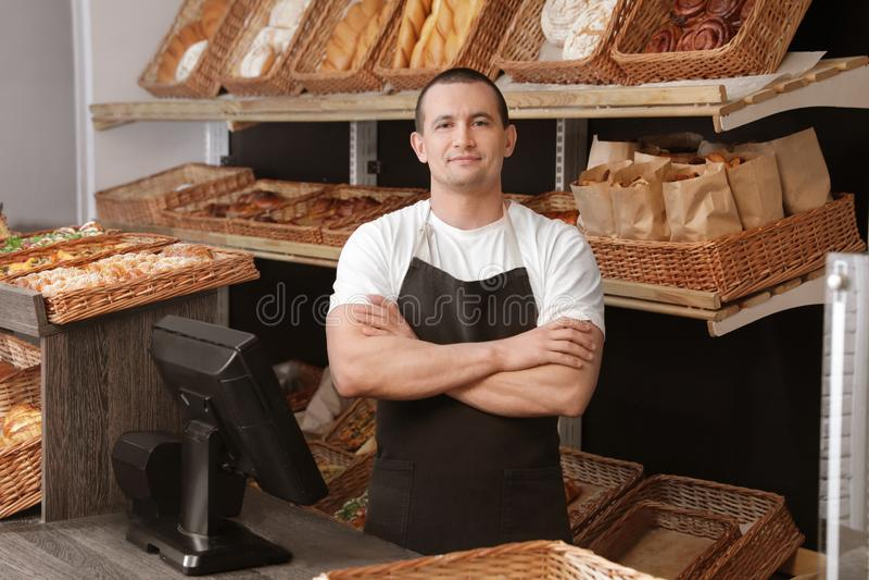 Retrato del panadero profesional en el escritorio de cajero cerca del escaparate fotos de archivo libres de regalías