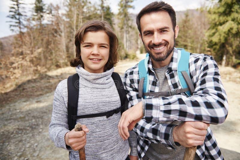 Retrato del papá y de su hijo con las mochilas en el bosque foto de archivo libre de regalías