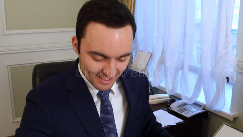 Retrato del papeleo joven feliz de la lectura del hombre de negocios en el escritorio en oficina y la sonrisa foto de archivo