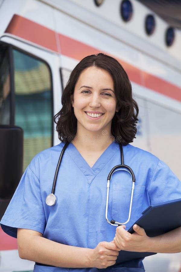 Retrato del paramédico de sexo femenino sonriente delante de la ambulancia de la  foto de archivo