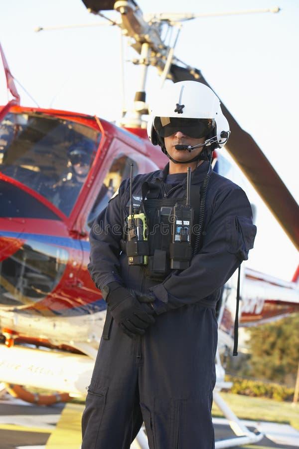 Retrato del paramédico que se coloca delante de helicóptero sanitario del ejército imagenes de archivo