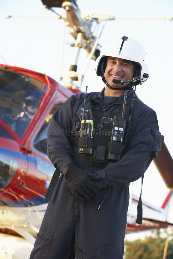 Retrato del paramédico que se coloca delante de helicóptero sanitario del ejército imagen de archivo libre de regalías