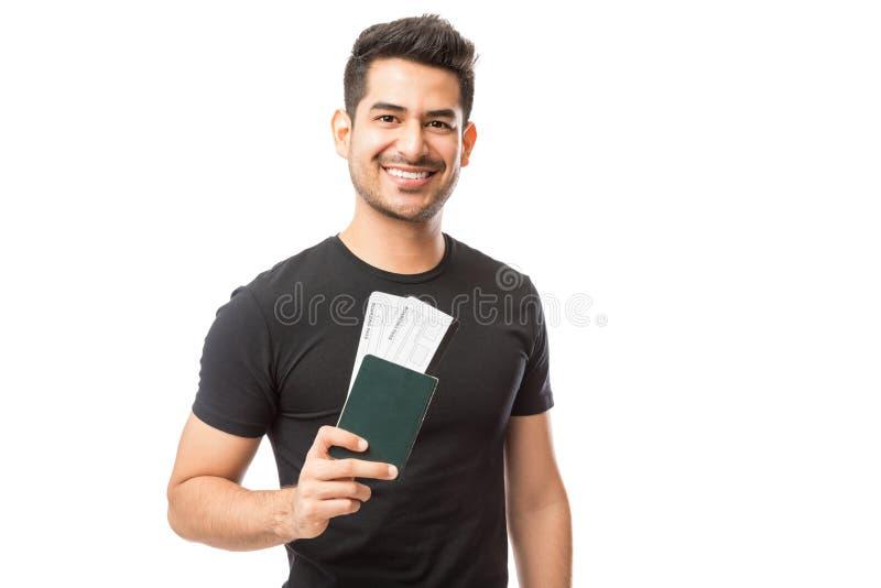 Retrato del paso joven feliz de Guy Holding Passport And Boarding foto de archivo libre de regalías