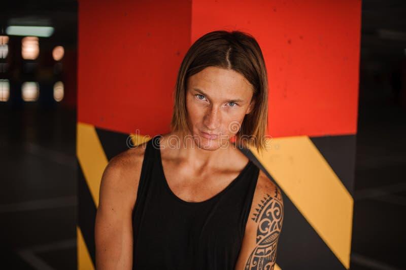 Retrato del pelirrojo joven atractivo y del hombre de pelo largo con el tatuaje fotografía de archivo