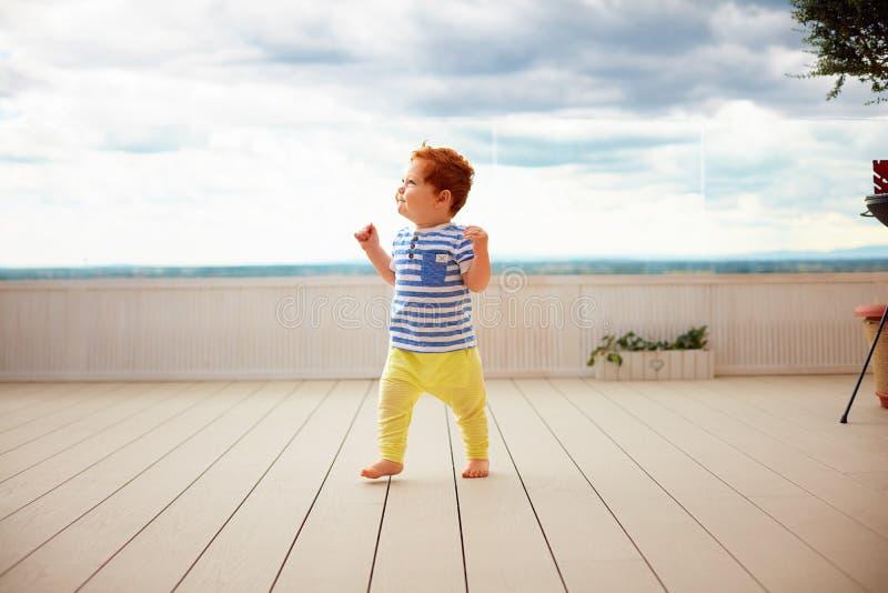 Retrato del pelirrojo lindo, bebé de un año que camina en decking fotos de archivo libres de regalías