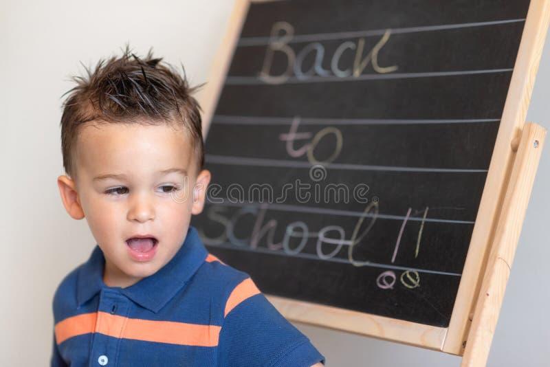 Retrato del pequeño alumno de la escuela primaria con el texto de nuevo a la escuela en la pizarra foto de archivo