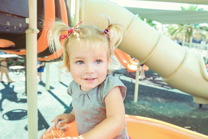 Retrato del pequeño bebé blondy sonriente emocional que sube en la diapositiva en el patio al aire libre del verano Foco selectiv fotografía de archivo libre de regalías