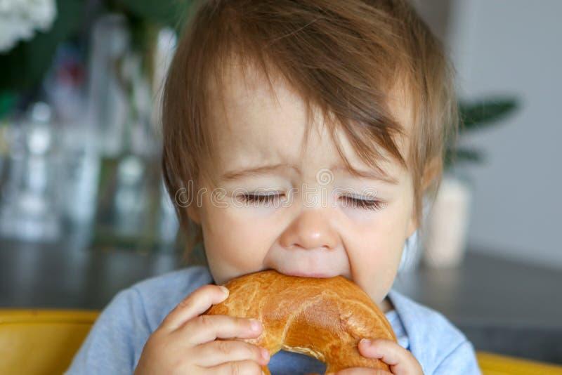 Retrato del pequeño bebé divertido que come el panecillo grande con los ojos cerrados, expresión de la cara de la diversión foto de archivo libre de regalías