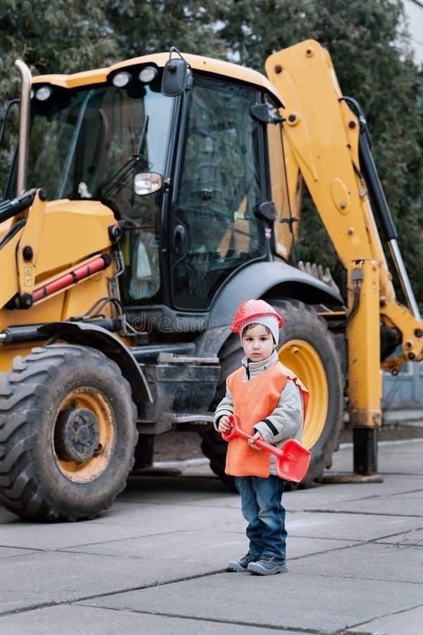 Retrato del pequeño constructor en los cascos de protección que trabajan al aire libre cerca del excavador del tractor fotos de archivo