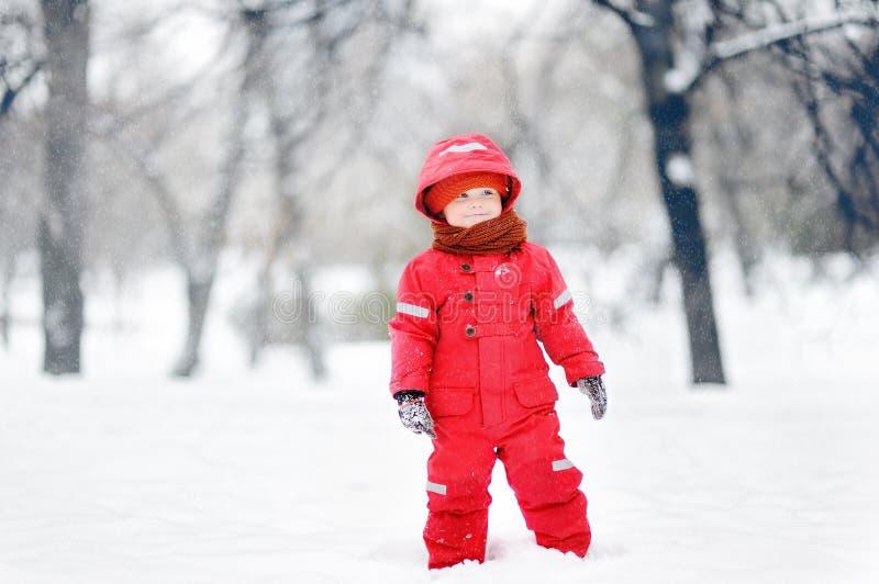 Retrato del pequeño muchacho divertido en la ropa roja del invierno que se divierte con nieve durante las nevadas foto de archivo libre de regalías