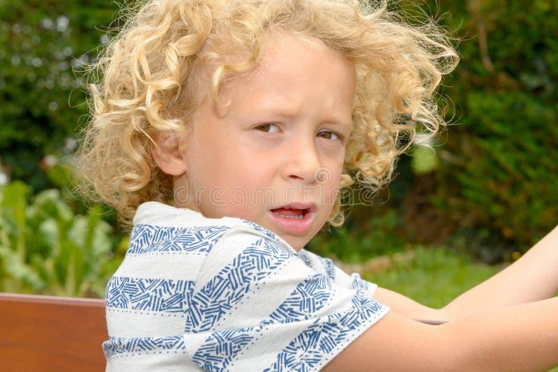 Retrato del pequeño muchacho rubio contrariedad foto de archivo libre de regalías