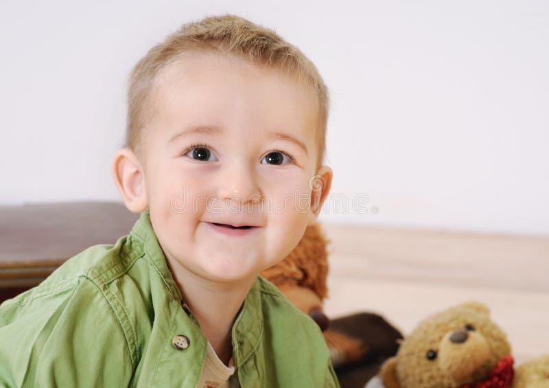 Retrato del pequeño muchacho sonriente lindo con su juguete en fondo fotos de archivo libres de regalías