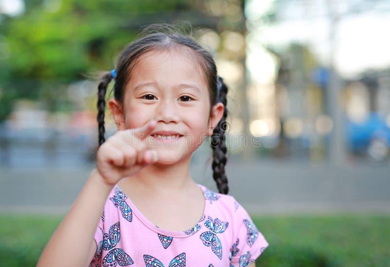 Retrato del pequeño niño asiático feliz en jardín con señalar en la cámara Muchacha sonriente del niño del retrato en parque del  fotografía de archivo libre de regalías