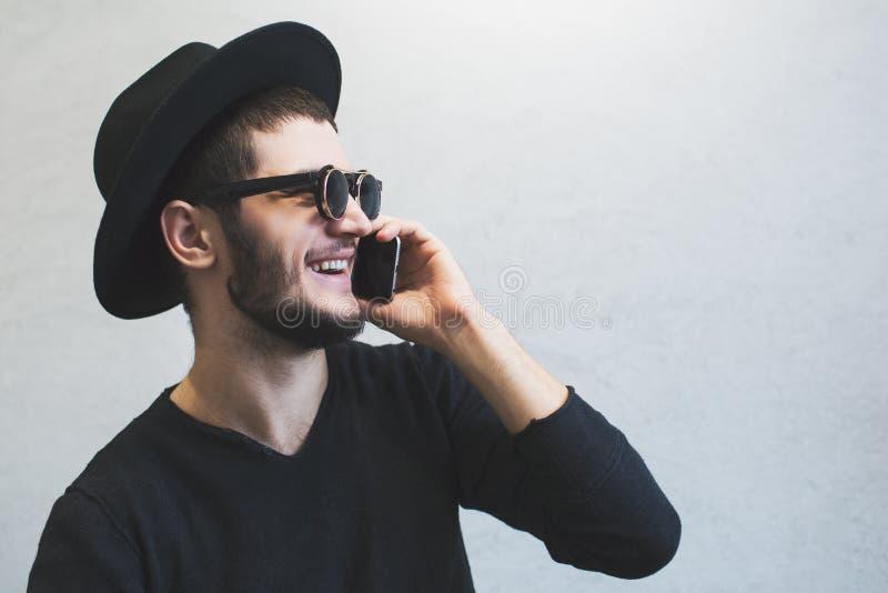 Retrato del perfil de reír al individuo joven que usando smartphone sobre el fondo blanco Gafas de sol y sombrero que llevan, ves fotografía de archivo