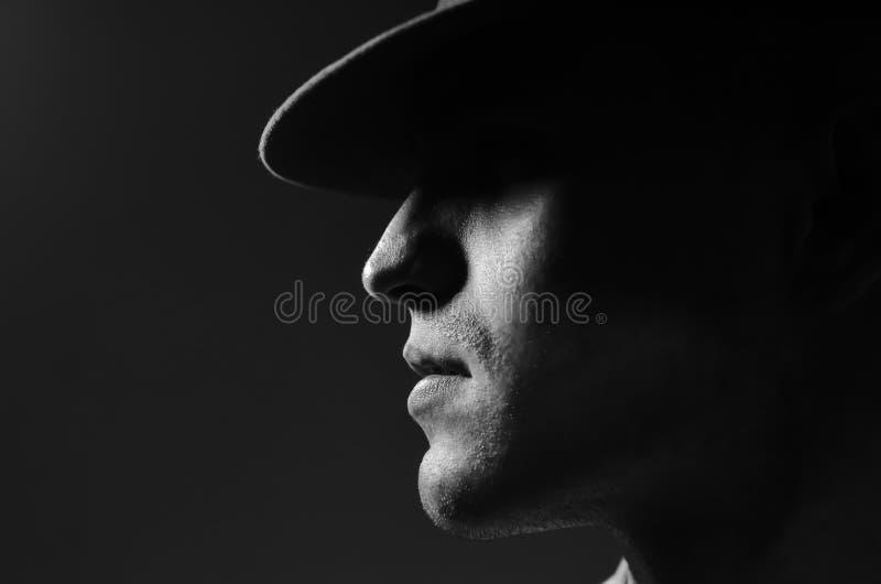 Retrato del perfil de un hombre joven en una situación del sombrero sobre fondo gris oscuro Cierre para arriba Estilo clásico Cop foto de archivo