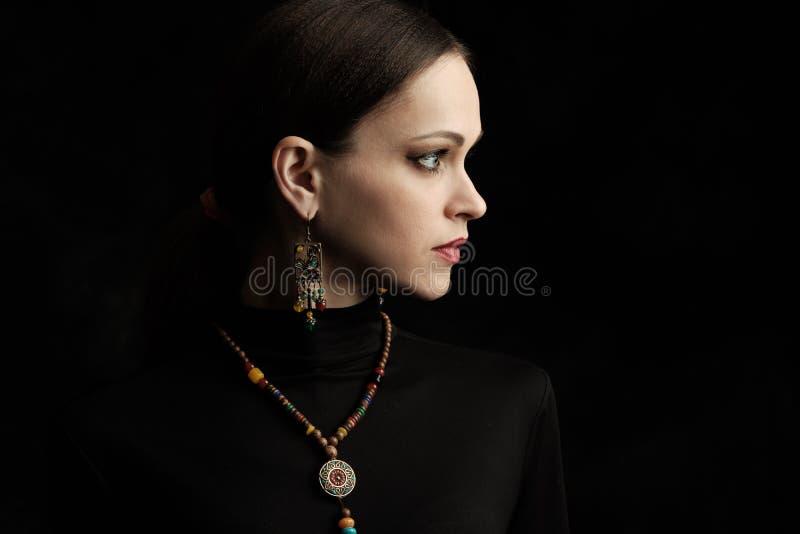 Retrato del perfil de una mujer hermosa que lleva la joyería étnica foto de archivo