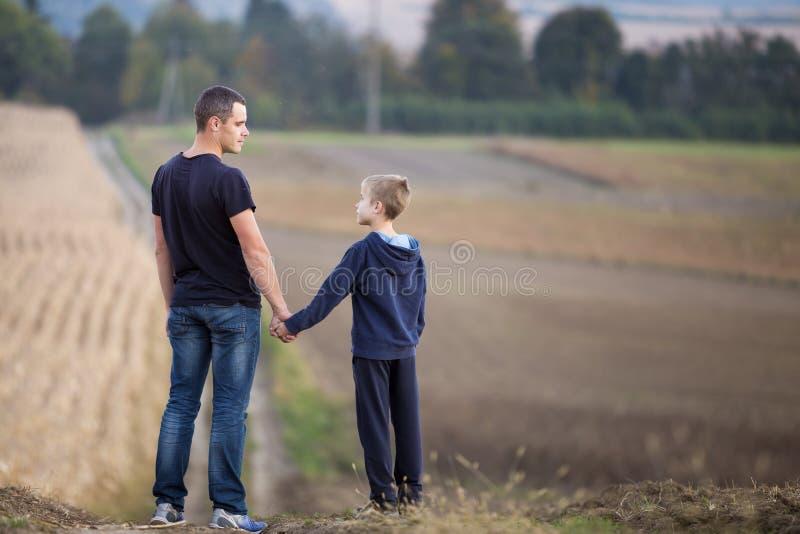 Retrato del perfil del padre joven y de la situación sonriente del hijo en el campo herboso que lleva a cabo las manos en árboles fotos de archivo libres de regalías