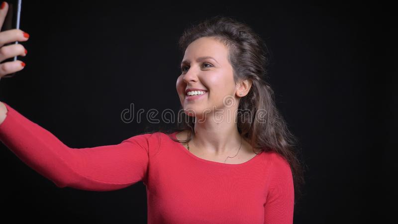Retrato del primer del caucásico de mediana edad atractivo que toma selfies en el teléfono y que sonríe delante de la cámara foto de archivo