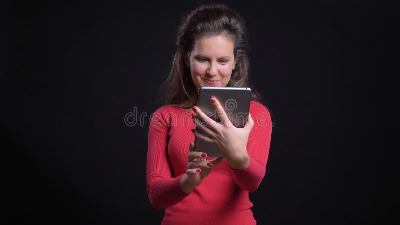 Retrato del primer del caucásico de mediana edad atractivo usando la tableta con el fondo aislado en negro imágenes de archivo libres de regalías