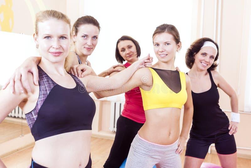Retrato del primer de cinco atletas de sexo femenino caucásicos felices que presentan junto abrazado contra Fitballs en gimnasio imagenes de archivo
