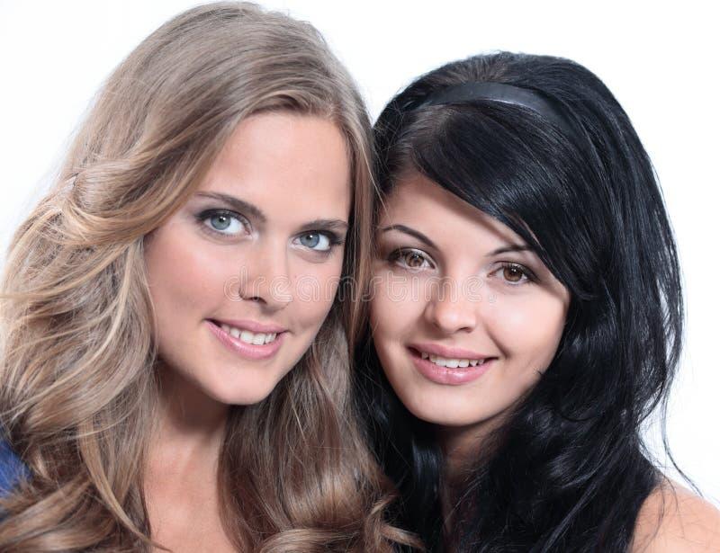 Retrato del primer de dos amigos femeninos jovenes sonrientes contra wh fotografía de archivo
