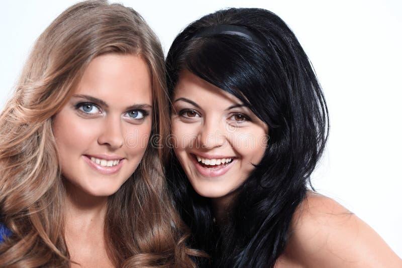 Retrato del primer de dos amigos femeninos jovenes sonrientes contra wh fotos de archivo