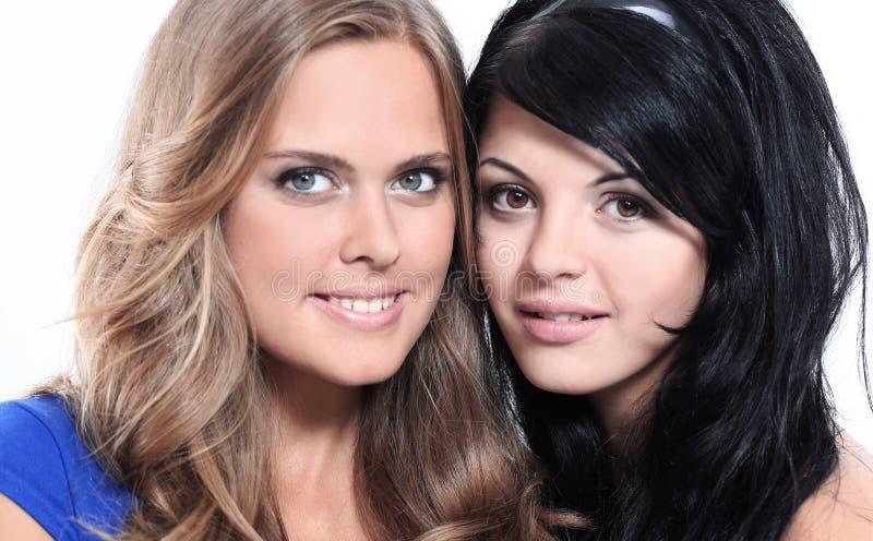 Retrato del primer de dos amigos femeninos jovenes sonrientes contra wh imágenes de archivo libres de regalías