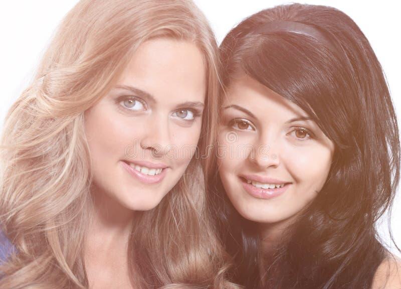 Retrato del primer de dos amigos femeninos jovenes sonrientes contra wh imagenes de archivo
