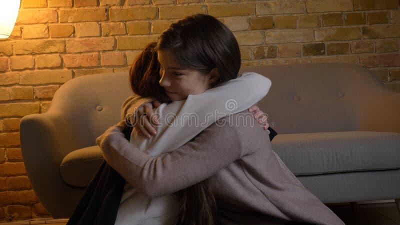 Retrato del primer de dos muchachas caucásicas bonitas jovenes que abrazan con amor dentro en un apartamento acogedor imagen de archivo