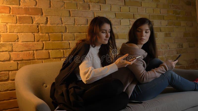 Retrato del primer de dos muchachas caucásicas bonitas jovenes que usan los teléfonos mientras que descansa sobre el sofá dentro  foto de archivo libre de regalías
