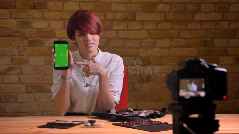 Retrato del primer de fluir video femenino atractivo joven del blogger vivo usando la tableta y de mostrar croma-llave verde fotos de archivo libres de regalías