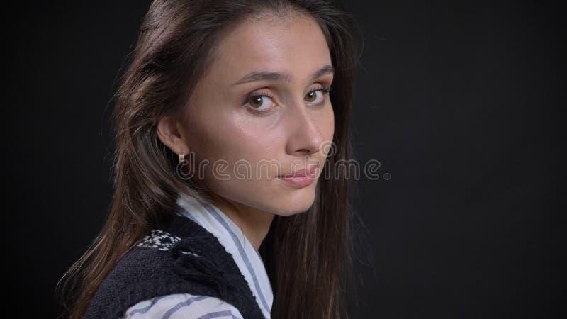Retrato del primer de la cara femenina caucásica linda joven con los ojos marrones y el pelo moreno que miran de torneado a la cá imagen de archivo libre de regalías