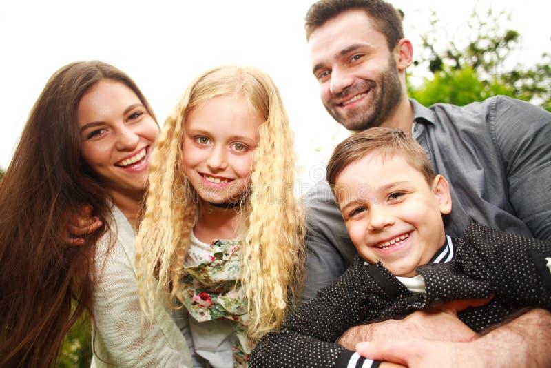 Retrato del primer de la familia sonriente feliz en parque de la ciudad fotografía de archivo libre de regalías