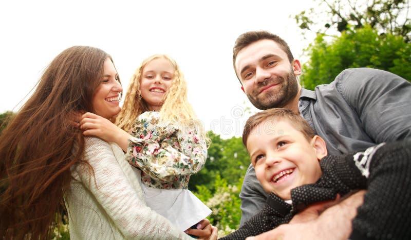 Retrato del primer de la familia sonriente feliz en parque de la ciudad imagenes de archivo