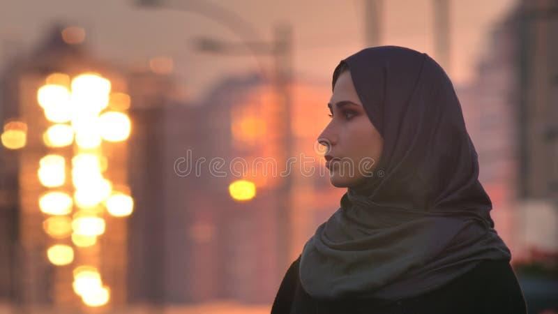 Retrato del primer de la hembra bonita joven en el hijab que da vuelta y que mira al lado con los edificios brillantes en imágenes de archivo libres de regalías