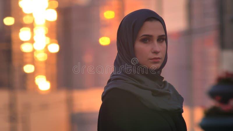 Retrato del primer de la hembra bonita joven en el hijab que gira y que mira la cámara con la ciudad urbana y que brilla edificio imágenes de archivo libres de regalías