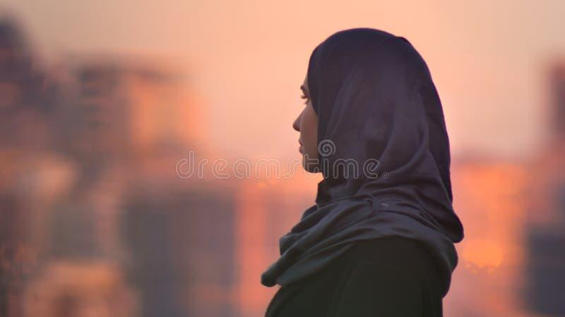 Retrato del primer de la hembra bonita joven en el hijab que mira adelante con el ambiente urbano y los edificios brillantes en imagen de archivo libre de regalías