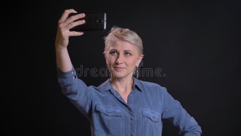 Retrato del primer de la hembra caucásica adulta con el pelo rubio corto que hace selfies en el teléfono y que presenta delante d fotos de archivo libres de regalías