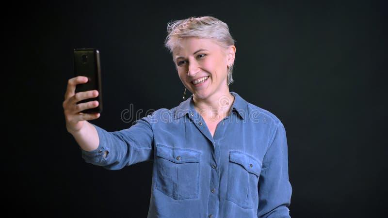 Retrato del primer de la hembra caucásica alegre adulta con el pelo rubio corto que hace selfies en el teléfono y que sonríe aden fotos de archivo libres de regalías