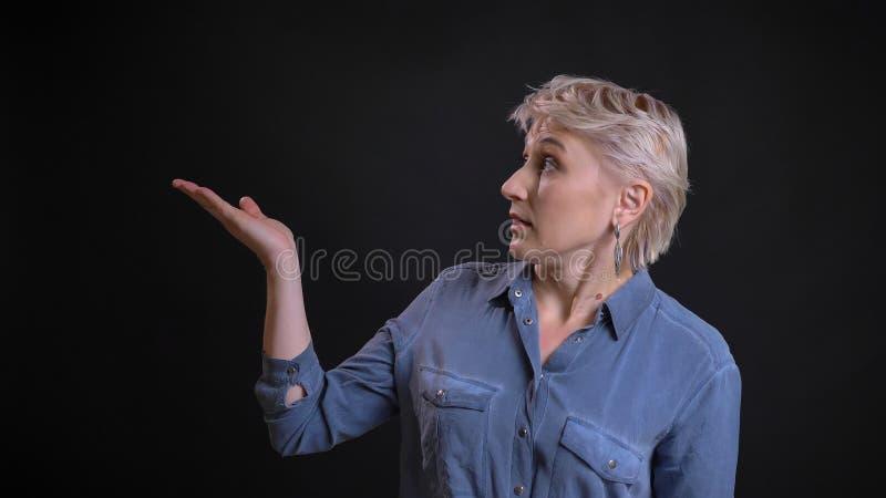 Retrato del primer de la hembra caucásica atractiva adulta que demuestra una presentación con su mano que señala en el lado foto de archivo