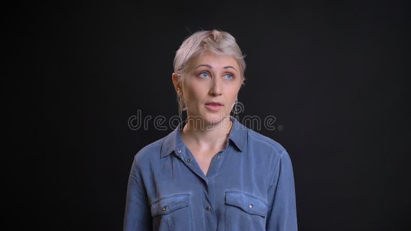 Retrato del primer de la hembra caucásica atractiva adulta que es irritada y que hace un rollo del ojo delante de la cámara con fotografía de archivo