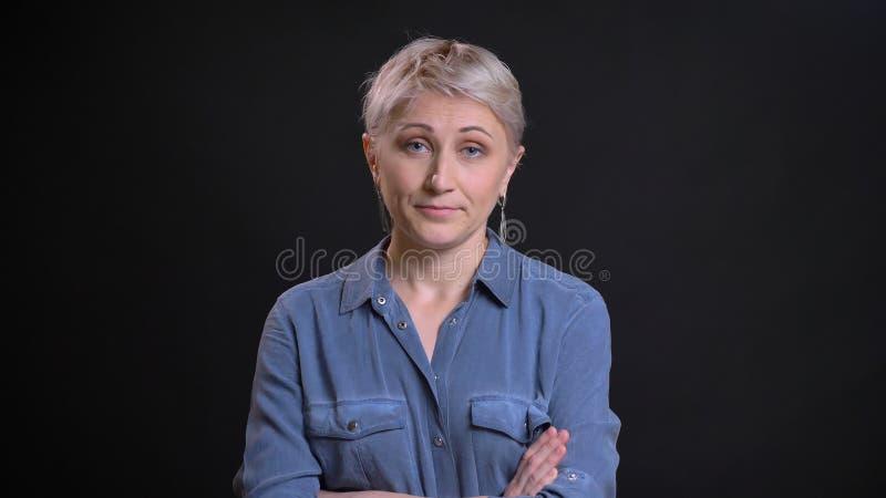 Retrato del primer de la hembra caucásica atractiva adulta que es molestada y haciendo sus brazos cruzar sobre el pecho que mira imagenes de archivo